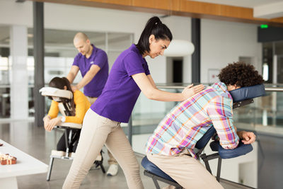 Woman and Man giving Corporate Chair Massage